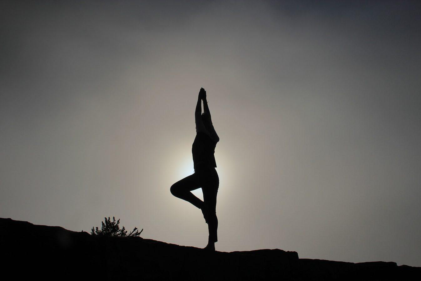 Silent disco yoga, een vrouw staat in yoga pose met armen opgeheven